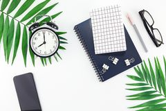 Top view flat lay office workspace desk styled design office supplies alarm clock tropical palm leaves smartphone copy space black. White background. Template stock photography