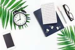 Top view flat lay office workspace desk styled design office supplies alarm clock tropical palm leaves smartphone copy space black. White background. Template stock images