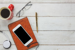Top view / Flat Lay the pen / note book / white mobile phone / listening radio music. By headphones / black coffee and eyeglasses on rustic table wooden.An idea royalty free stock images