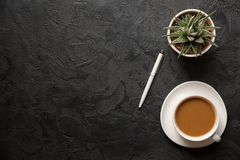 Top view flat lay shot of office desk table. Cup of cappucino coffee, plant pot and pen on dark background. Copy space.  royalty free stock photo