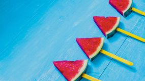 Top view, flat lay, skewers of watermelon slices and mint on bright blue wood background,concept organic fruit  non-toxic for. Health,for refreshing and fun in stock photos