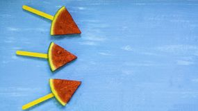 Top view, flat lay, skewers of watermelon slices and mint on bright blue wood background,concept organic fruit  non-toxic for. Health,for refreshing and fun in stock photography