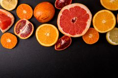 Top view, flat lay. Sliced citrus on a black background. Copy space. Fruits are laid out on top