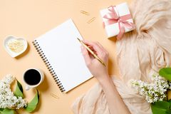 Free Top View, Flat Lay Women Desk With Lilac Flowers, Silk Scarf, Coffee Cup, Gift Box, Human Hand Holding Golden Pen And Writing In Stock Photos - 149710263