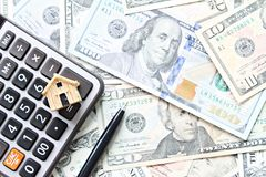 Top view or flat lay of wood house model, calculator and pen on American Dollars cash money stock photography