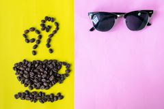 Top view flat layer coffee beans in cup and smell icon shape, with vintage wooden coffee grinder, phone,  sun glasses and blank bo. Ok on two tone multicoloured Royalty Free Stock Image