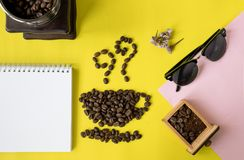 Top view flat layer coffee beans in cup and smell icon shape, with vintage wooden coffee grinder, phone,  sun glasses and blank bo. Ok on two tone multicoloured Royalty Free Stock Photo