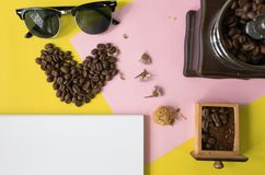 Top view flat layer heart smile  icon shape ,sun glasses, vintage wooden coffee grinder and blank book for copy space  on two tone. Top view flat layer heart Stock Photos