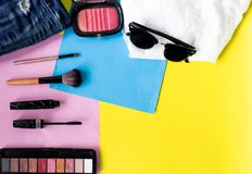 Top view flat layer travel life style with beauty make up set, mascara, brushes, eye shadow palate, and brush on, ripped jeans , s. Un glasses and hat on tree stock photo