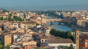 Top view of Florence city timelapse at sunrise with arno river bridges and historical buildings. Mountains on background. Green trees, blue cloudy sky at stock video footage