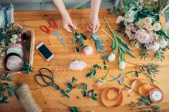 Top view of florist hands arranging and decorating flowers. Royalty Free Stock Image