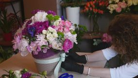Top view of florist hands making flower bouquet with decorative ribbon stock video footage