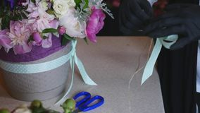 Top view of florist hands making flower bouquet with decorative ribbon stock video