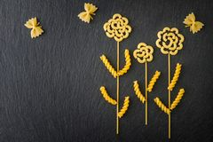 Top view flowers and butterflies made out of various pasta on the dark slate background. Top view flowers and butterflies made out of various pasta on the dark royalty free stock photos