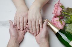 Male and female hands of elderly couple.Valentine`s Day concept. Top view of flowers,champagne on marble table.Dating concept Top view of wine bottle, pink roses stock photos