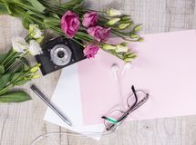 Top view of flowers, vintage camera, earphones, pen, glasses and Royalty Free Stock Photo