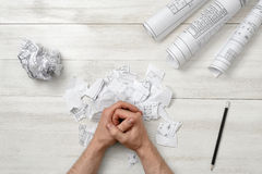 Top view of folded hands man on wooden surface with architect drawing Stock Images