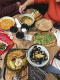 Top view of food dishes and hands, dinner, lunch together, family, friends eat, cuisine of different nations. Appetite, hunger concepts stock photography
