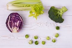Top view of food: healthy fresh vegetables on a white wooden table-cabbage, broccoli and Brussels sprouts and red. Top view of the assorti of cabbage, broccoli Stock Image