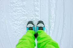 Top view of a foot in the snowboard boots and bright pants Royalty Free Stock Photos