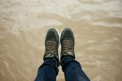 Top view. foot of women wearing shoe, jeans stand on water surface are background. image for. Top view. foot of women wearing shoe, blue jeans stand on water royalty free stock image