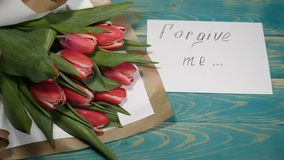 Top view of a forgive me message and Tulips flowers bouquet on a wooden table. Couple relationship concept. Shot in 4 k. Top view of a forgive me message and stock footage