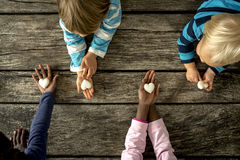 Top view of four children of mixed races each holding a marble h royalty free stock image
