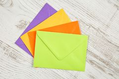 Top view of four colorful sealed envelopes from recycled paper on a white rustic wooden table royalty free stock photography