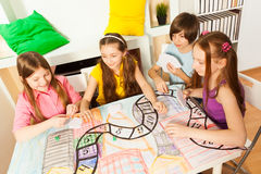 Top view of four kids playing the tabletop game. Top view of four kids sitting at the table, playing the tabletop game with cards stock images