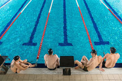 Top view of four male swimmers. Sitting on the edge of a swimming pool Stock Photography