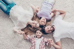 Top view of four relatives, lying on the beige cozy carpet at ho. Me, holding hands, all smiling, wearing casual outfits Royalty Free Stock Images