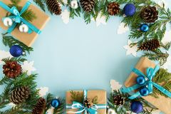 Top view on frame from Christmas decorations, gift boxes, fir branches and pine cones on the blue background. Stock Photography