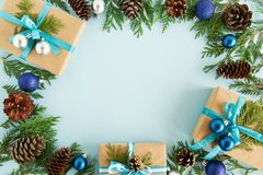 Top view on frame from Christmas decorations, gift boxes, fir branches and pine cones on the blue background. Royalty Free Stock Photos