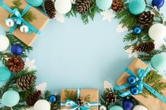 Top view on frame from Christmas decorations, gift boxes, fir branches, pine cones and Christmas lights on the blue background. Royalty Free Stock Image