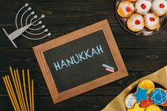 Frame with hanukkah word. Top view of frame with hanukkah word, donuts and cookies with star of david on wooden tabletop Royalty Free Stock Photography