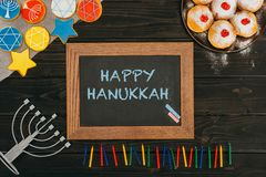 Frame with happy hanukkah. Top view of frame with happy hanukkah, donuts and cookies with star of david on wooden tabletop Royalty Free Stock Photos