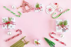 Top view on a frame from red, green and silver Christmas decorations, gift boxes and fir branches on a pink background. stock images
