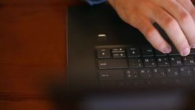 Top view of freelancer`s hands typing on laptop keyboard in cafe. Businessman working in office. Man searches. Information on internet at coffeeshop stock video footage