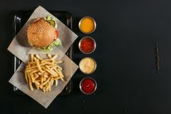 Top view of french fries with delicious burger on tray and assorted sauces. On black stock image