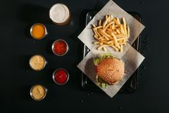 Top view of french fries and tasty burger on tray, glass of beer and assorted sauces. On black royalty free stock photography