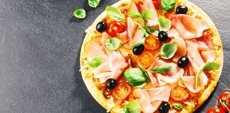 Top view of fresh appetizing pizza on dark stock photos