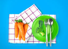Top view of fresh broccoli and carrots in green dish and towel o. The top view of fresh broccoli and carrots in green dish and towel on vibrant color background Royalty Free Stock Image