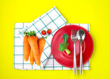 Top view of fresh broccoli a, carrots and tomato with red dish a Stock Photography