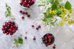 Top view Fresh cherry fruit in glass vase, other dishes with berries and jar with jasmine and wildflowers on the light marble tabl. E. Soft selective focus royalty free stock photo