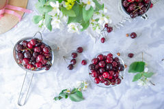 Top view Fresh cherry fruit in glass vase, other dishes with berries and jar with jasmine and wildflowers on the light marble tabl. E. Soft selective focus royalty free stock image