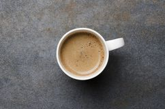 Top view of fresh coffee espresso or latte with frothy foam on gray table, empty space royalty free stock image