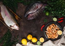 Top view of fresh fish, chili peppers, shrimp, herbs with lemons and tablecloth Royalty Free Stock Photos