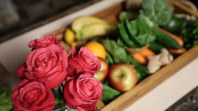 Top view of fresh fruits and vegetable in tray. Top view of fresh fruits and vegetables in wooden tray on kitchen table closeup. Selective focus on bouquet of stock footage