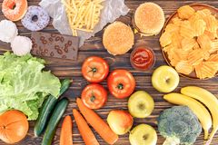 Top view of fresh fruits with vegetables and assorted unhealthy food. On wooden table royalty free stock photo