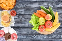 Top view of fresh fruits with vegetables and plates with junk food on wooden table stock photos